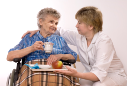 a caregiver giving some meals to the elderly