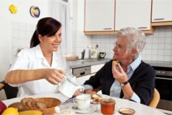 caregiver serving food to an elderly lady